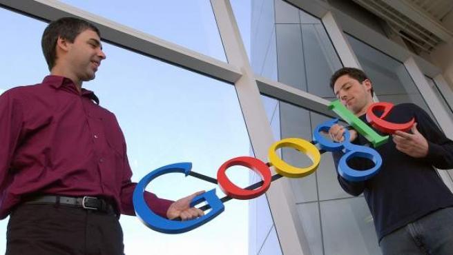 Larry Page y Sergey Brin sostienen el logotipo de Google.