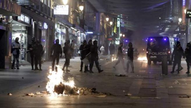 Varios fuegos arden en la calle de Preciados ante la mirada de los antidisturbios.