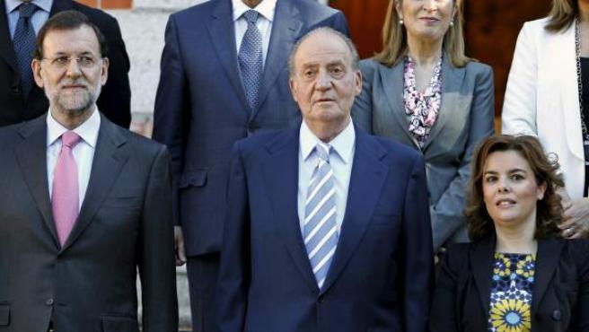El rey Juan Carlos, junto al presidente del Gobierno, Mariano Rajoy , y la vicepresidenta, Soraya Sáenz de Santamaría, este viernes en el Palacio de la Zarzuela.
