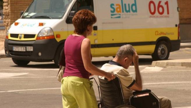 Una mujer lleva en silla de ruedas a un anciano en Zaragoza.