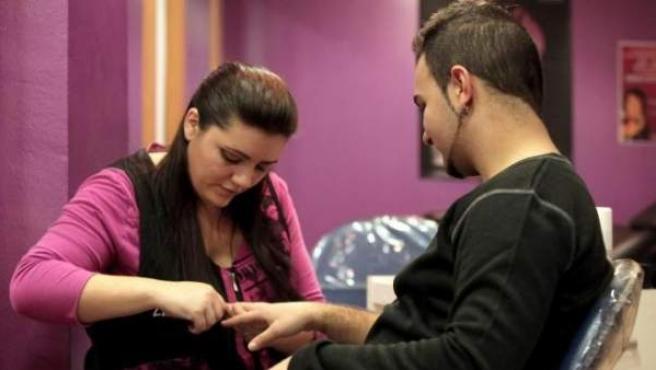 Una peluquera le hace la manicura a un cliente en Cataluña.