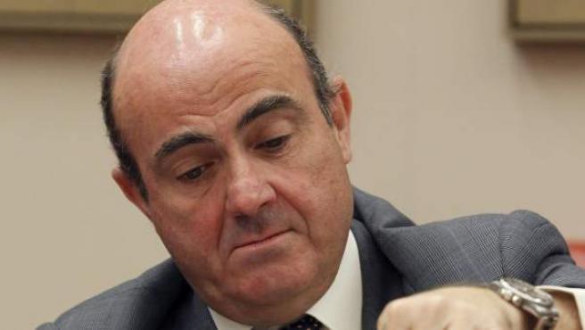 El ministro de Economía, Luis de Guindos, se sirve agua poco antes de comparecer en la comisión correspondiente del Congreso.