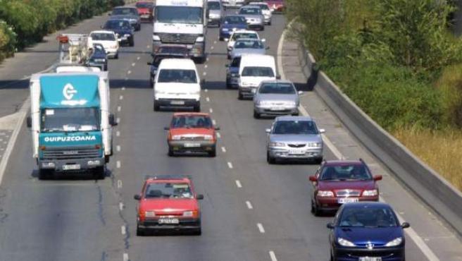 Varios vehículos circulan por una carretera en un momento de retención.