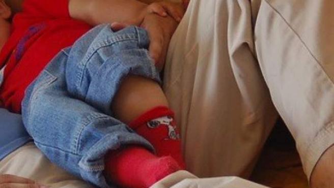 Un niño durmiendo la siesta en el sofá junto a su madre.