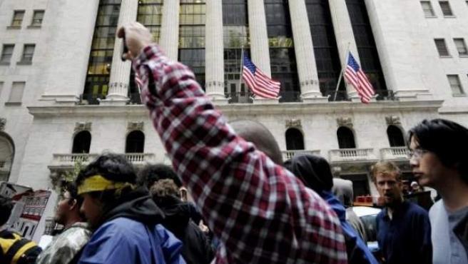Un grupo de jóvenes se manifiesta ante la sede de la bolsa de Nueva York, en protesta contra el sistema económico.