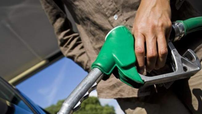 Una mujer echa gasolina en su coche.