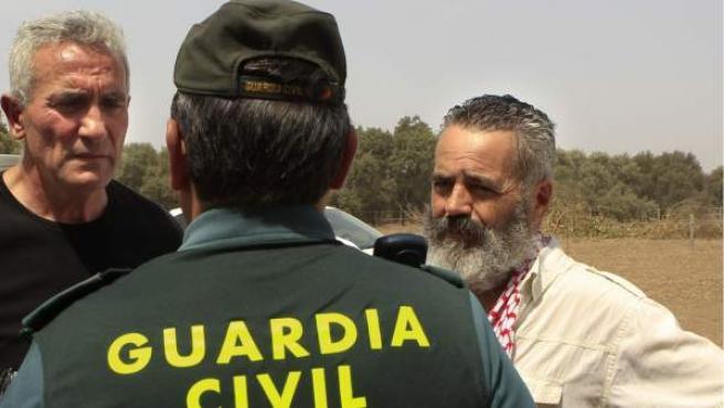 Un capitán de la Guardia Civil conversa con los líderes del Sindicato Andaluz de Trabajadores Juan Antonio Sánchez Gordillo (dcha.) y Diego Cañamero.