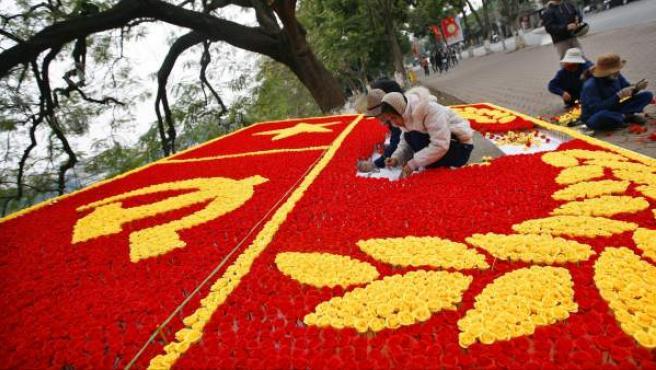 Varias personas trabajan en un aviso hecho de flores para el Congreso Nacional del Partido Comunista de Vietnam.