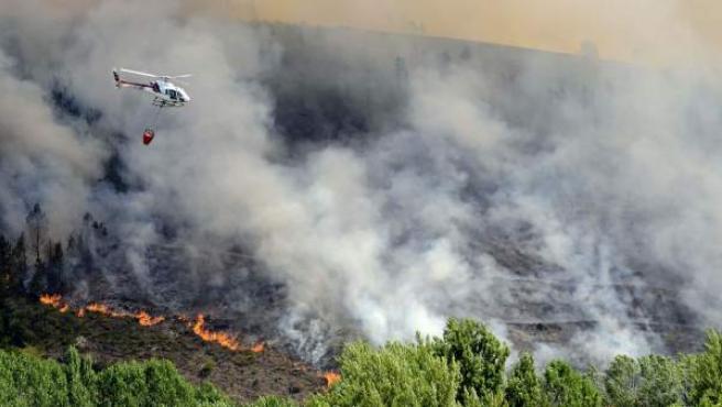 Un helicóptero sobrevuela una zona incendiada cercana al pueblo de A Veiga de Cascallá, desalojado a causa del incendio iniciado en O Barco de Valdeorras (Ourense).