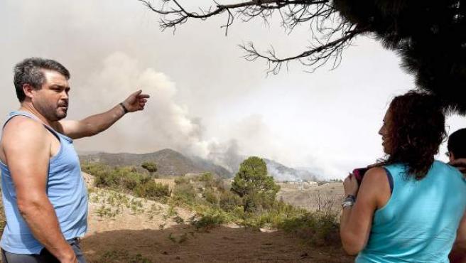 Unos vecinos contemplan la columna de humo del incendio que afecta al municipio de El Tanque en Tenerife.