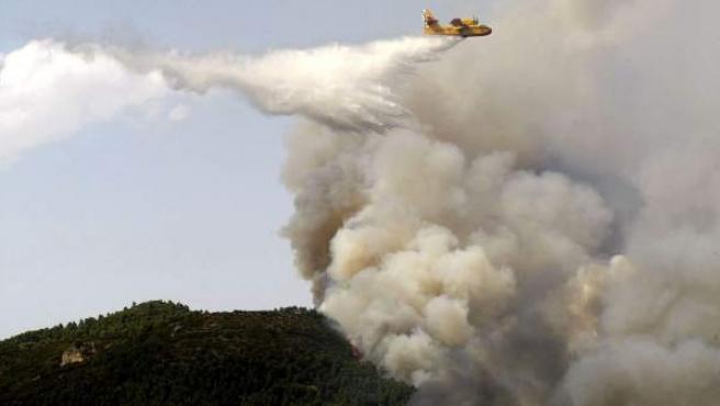 Un hidroavión realiza una descarga en el incendio declarado en el término municipal de La Torre de les Maçanes (Alicante).