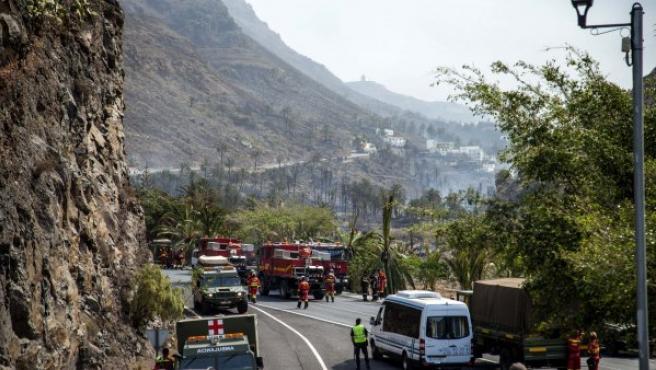 arios coches de bomberos cortan el tráfico en el límite del incendio forestal en la isla de La Gomera.