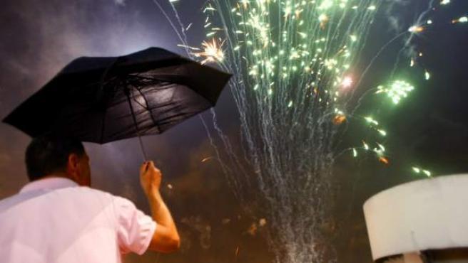 Vecinos de Elche (Alicante) siguen desde una azotea el espectáculo pirotécnico que se celebra en la tradicional Nit d'Albà, con motivo de las fiestas en honor a la Virgen de la Asunción. Un imprevisto causó al menos 103 heridos, seis de ellos graves.