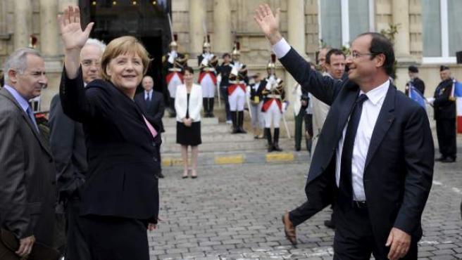 François Hollande (dcha.), y Angela Merkel (izda.), durante una ceremonia para conmemorar el 50 aniversario de la reconciliación franco-alemana en Reims.