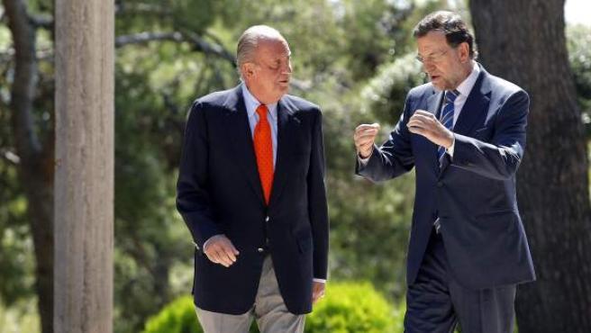 El rey Juan Carlos y el presidente del Gobierno, Mariano Rajoy, pasean por los jardines del Palacio de Marivent.