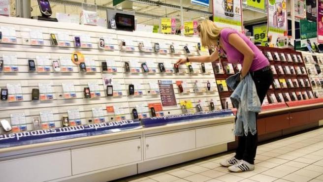 Una mujer mira teléfonos móviles en una gran superficie.