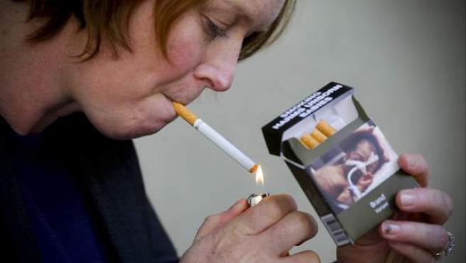 Una mujer australiana enciende un cigarrillo de un paquete sin marca.