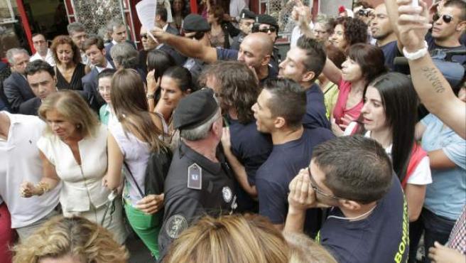 La alcaldesa de Madrid, Ana Botella (izda), abucheada por bomberos que protestan por su situación laboral.