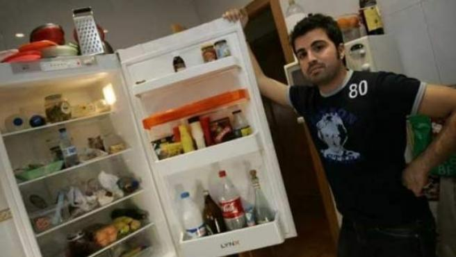 Un estudiante muestra el frigorífico que comparten todos los compañeros del piso.