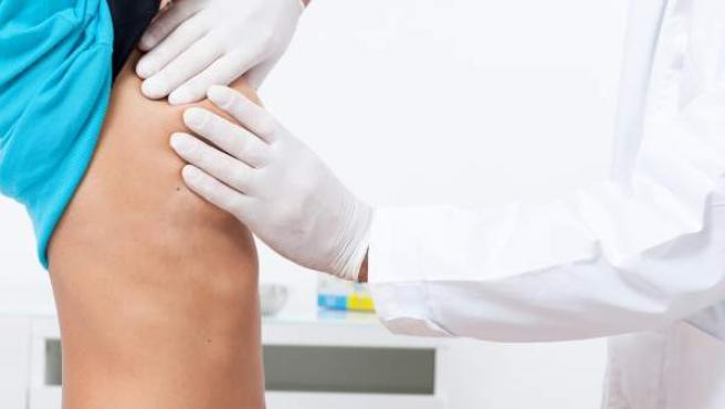 Un médico examina el pecho de una mujer.