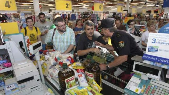 El diputado de IU en la Asamblea de Extremadura Víctor Casco (i), y el excoordinador general de la coalición en la región Manuel Cañada (c), en un supermercado en Extremadura ocurrido el pasado verano.