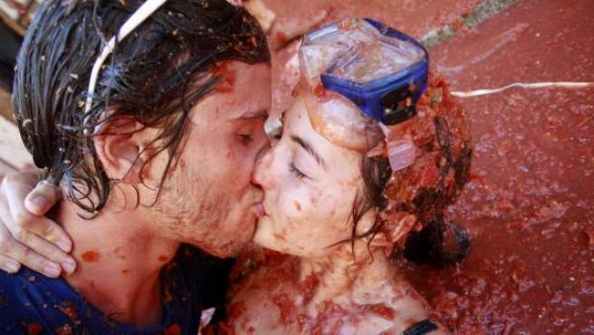 Una pareja se besa mientras participan en la tradicional fiesta de Buñol, la Tomatina, que en su edición de 2012 ha empleaso 120.000 kilos de tomates y ha contado con la presencia de 40.000 personas.
