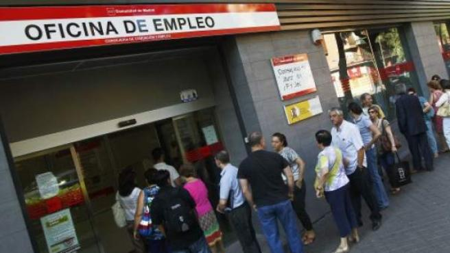 Un grupo de personas esperan a la puerta de una de las oficinas de empleo de Madrid.