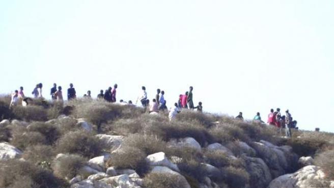Vista de varios de los 81 inmigrantes que permanecen en la Isla de Tierra, de soberanía española, llegados en dos grupos la semana pasada a esta isla, situada en el archipiélago de Alhucemas y a escasos 30 metros de la costa marroquí.