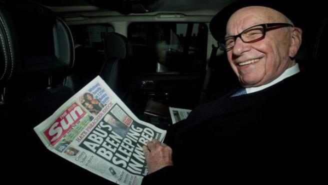 El magnate Rupert Murdoch lee un ejemplar del diario 'The Sun' al salir de su casa en Londres (Reino Unido).