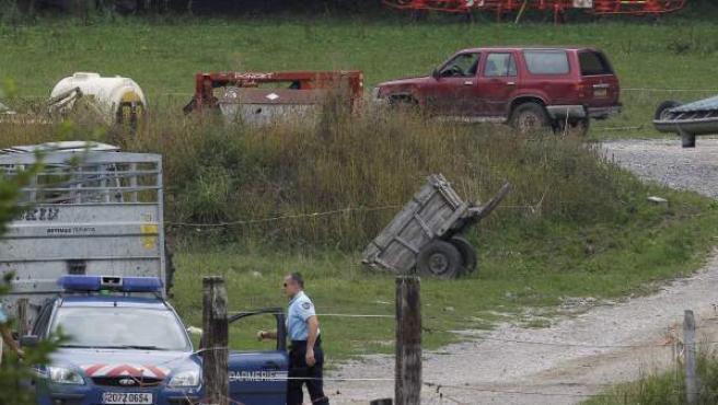 El coche, al fondo, en el que aparecieron cuatro muertos a balazos, en Francia.