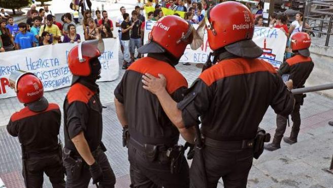 Agentes de la Policía Foral impiden a un grupo de distintas organizaciones estudiantiles entrar al edificio de El Sario de la Universidad Pública de Navarra, en el que se celebraba el acto académico.