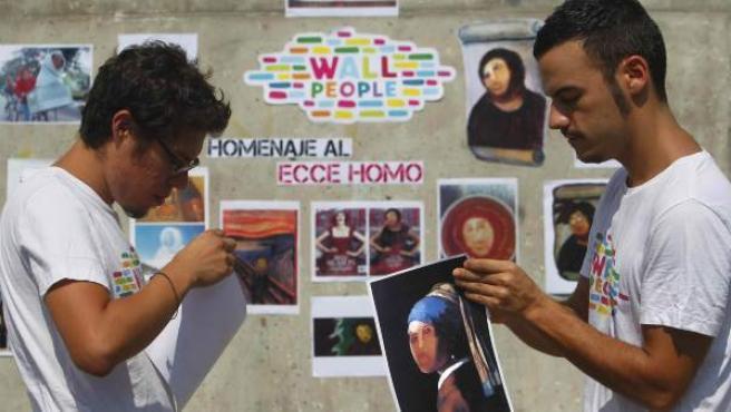 Dos jóvenes de Wallpeople colocan las obras de la exposición en homenaje al eccehomo.