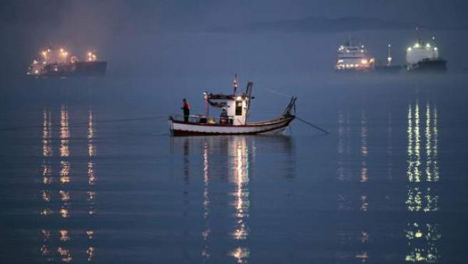 Un pesquero faena en la bahía de Algeciras alejado del Peñón de Gibraltar.