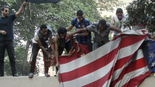 Manifestantes egipcios arrancan una bandera estadounidense durante una protesta convocada frente a la embajada de EE UU.