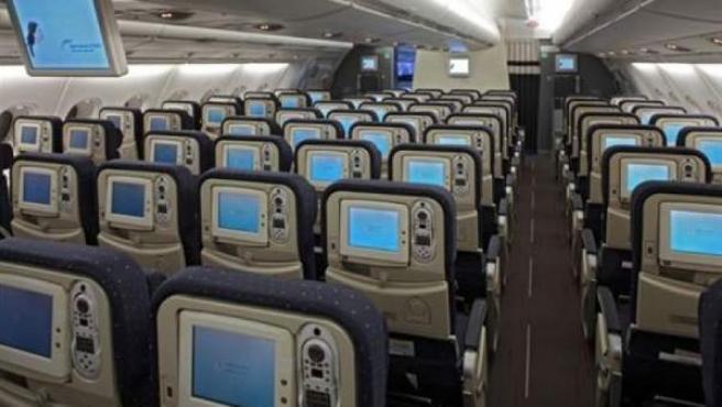Interior de un avión con todos sus asientos vacíos.