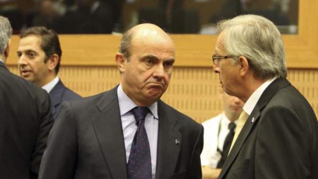 El ministro español de Economía, Luis de Guindos, conversa con el presidente del Eurogrupo, Jean-Claude Juncker.