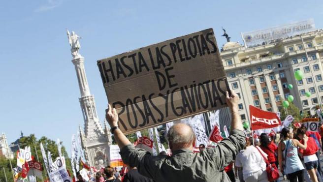 Un hombre que ha asistido a la 'Gran Marcha' de este 15-S sujeta, frente a Colón, una pancarta que reza 'Hasta las pelotas de rosas y gaviotas'.