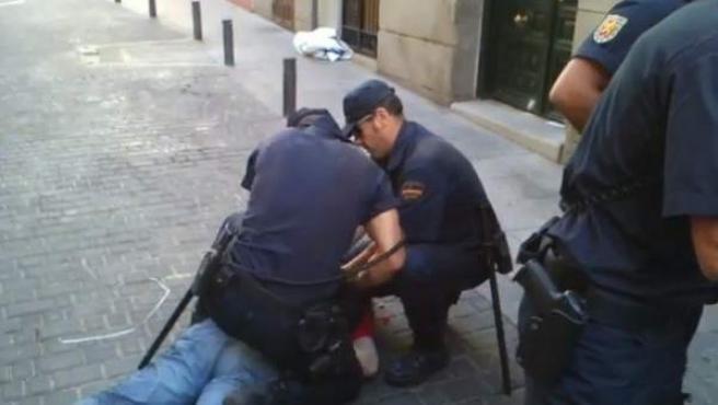 Los policías detienen a una persona durante las protestas del 15-S contra los recortes del Gobierno.
