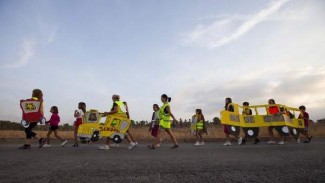 Los niños caminan por las carreteras que separan sus casas del colegio. Ayer llevaban carteles reivindicativos con forma de autobús.