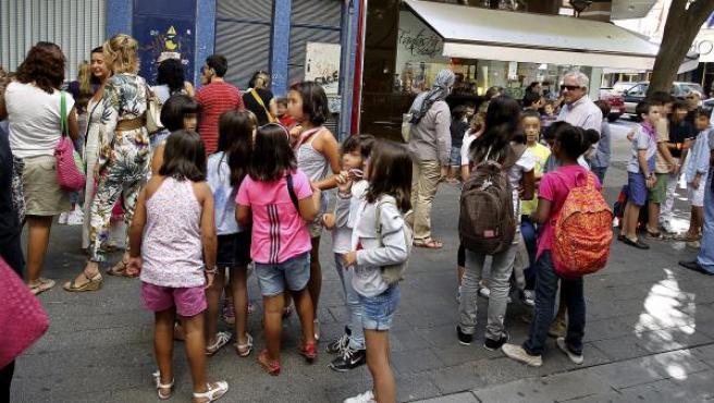 Varios niños, a la entrada de un colegio.