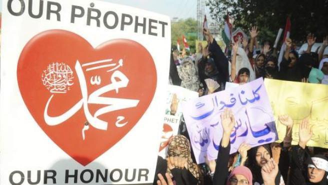 """Seguidoras de la organización Minhaj al-Qurán participan en Pakistán en una de las protestas convocadas contra la película 'La inocencia de los musulmanes'. En el cartel se lee: """" Nuestro profeta, nuestro honor""""."""