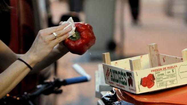 Voluntarios recogiendo alimentos en los cubos de basura.