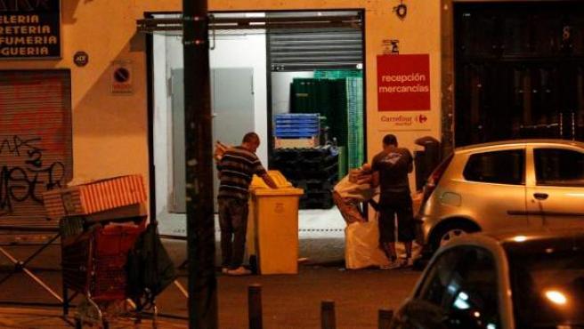 Un grupo de personas busca comida en contenedores de un supermercado de Madrid.