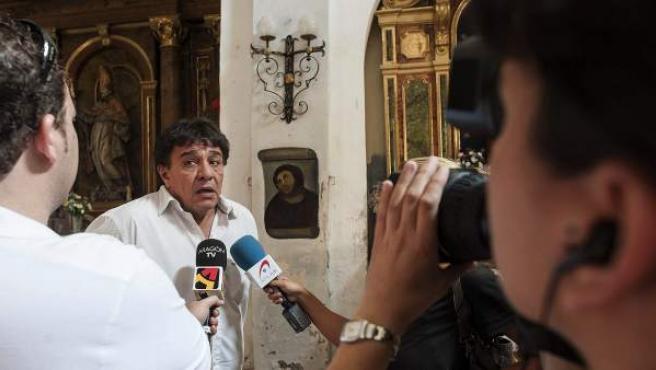 El alcalde de Borja, Miguel Arilla, en declaraciones a la prensa ante la imagen del Ecce homo destrozado por una anciana, en el Santuario de Misericordia. Expertos restauradores se han trasladado a esta localidad para analizar la pintura y estudiar su posible recuperación.