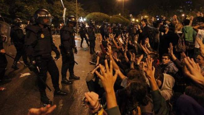 Un grupo de manifestantes se sienta ante los antidisturbios para evitar más cargas policiales.