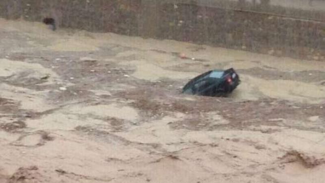 Un coche arrastrado por la riada en una rambla