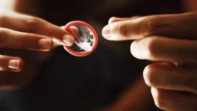 Una mujer entrega a su pareja un preservativo.