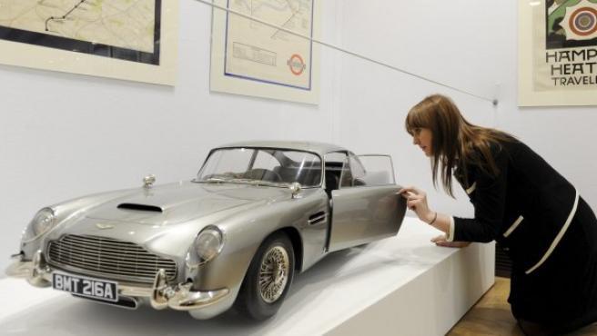 Una trabajadora de la casa de subastas Christie's posa para los fotógrafos junto a una réplica a escala 1/3 del Aston Martin DB5 utilizando en la película 'Skyfall'.