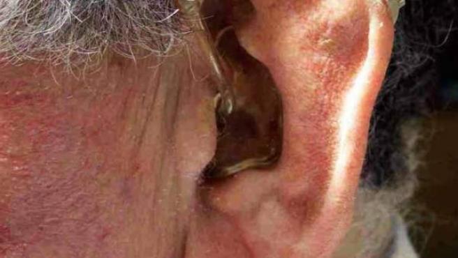 Un anciano con un aparato de audición en su oído.