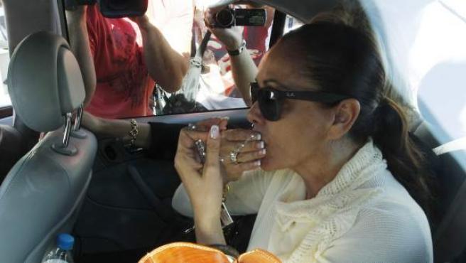 La tonadillera Isabel Pantoja, en el interior de su coche besa una medalla en las manos tras finalizar la sesión del juicio por blanqueo de capitales en el que también están acusados su expareja Julián Muñoz, que fue alcalde de Marbella, y la exesposa de éste, Maite Zaldívar y que ha arrancado en la Ciudad de la Justicia de Málaga.